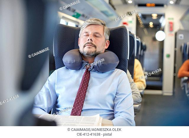 Tired businessman with neck pillow sleeping on passenger train