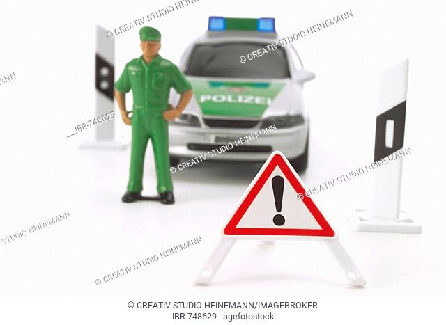 Toy police car, police officer, road marker and warning triangle