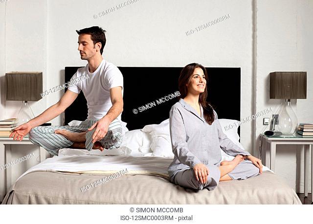 couple meditating in bedroom