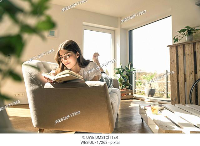 Relaxed young woman lying on couch reading a book