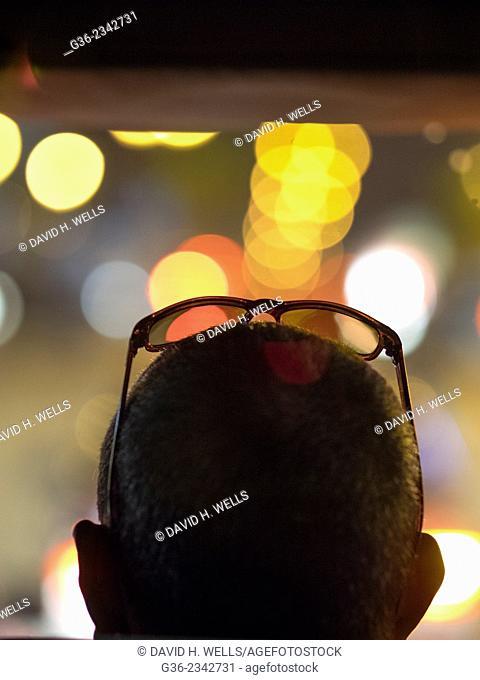 Silhouette of man wearing sunglasses against defocused lights in Casablanca, Morocco