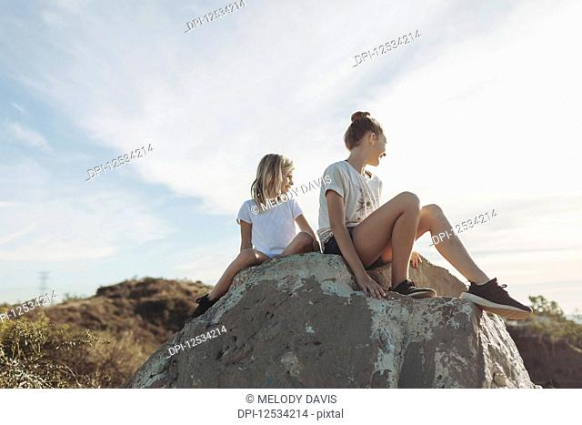Two girls sit on a boulder looking out; Los Angeles, California, United States of America