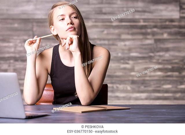 Thoughtful girl in tank top and pencil in hand sitting at wooden desk with laptop and notepad