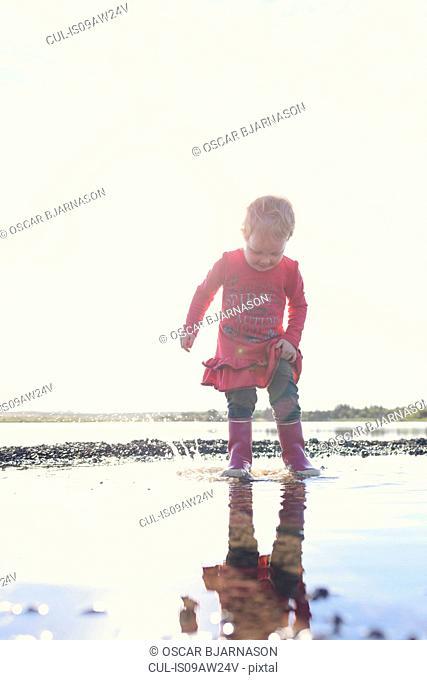 Girl wearing rubber boots splashing in lake, Hafravatn, Iceland