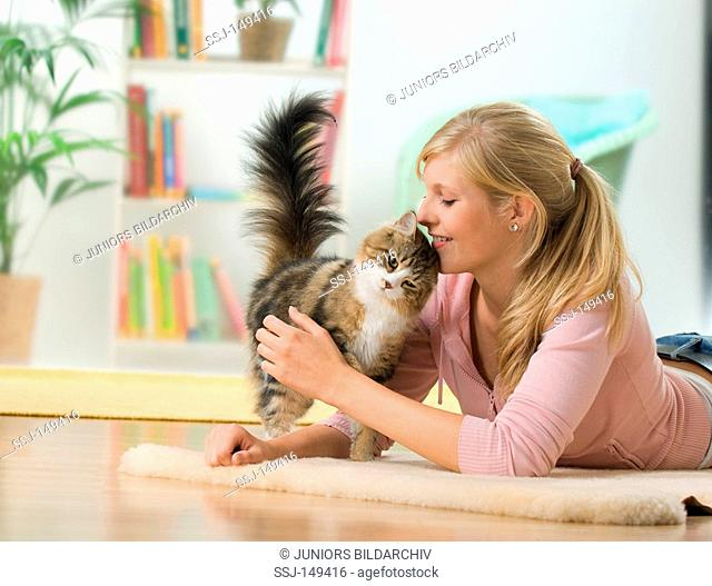 young woman smooching with Maine Coon cat