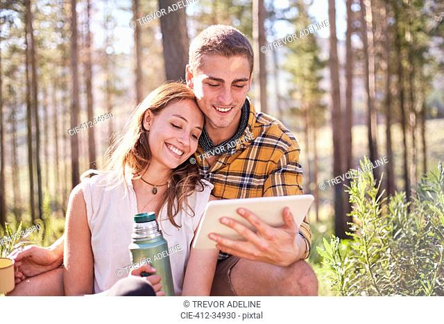 Young couple camping, drinking coffee and using digital tablet in sunny woods