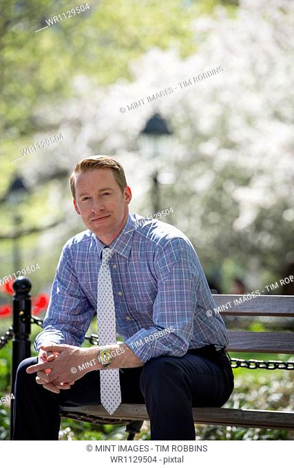 A businessman in a shirt with white tie, sitting on a park bench under the shade of a tree with blossom