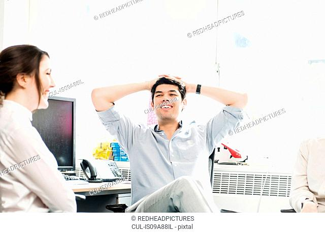 Colleagues in office, man with hands behind head