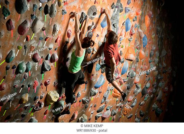 Young woman and mid adult man climbing on wall