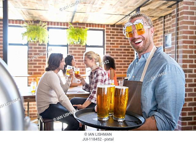 Barman Wearing Novelty Glasses Serving Customers In Bar