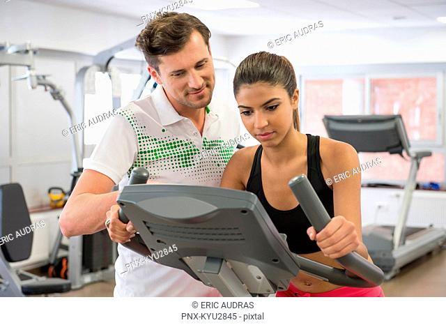 Instructor teaching a woman in spinning class at gym