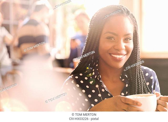 Portrait smiling African woman drinking cappuccino in cafe