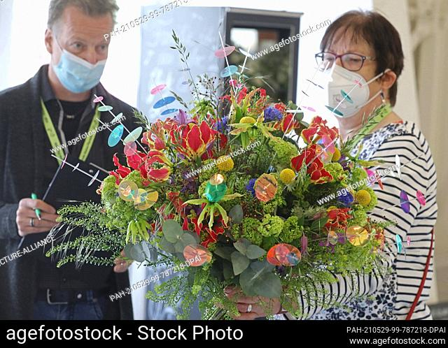 29 May 2021, Thuringia, Erfurt: Jury members Gerda Prinz (r) and Frank Tichless judge a competition bouquet at the Hesse-Thuringia State Florist Championships...