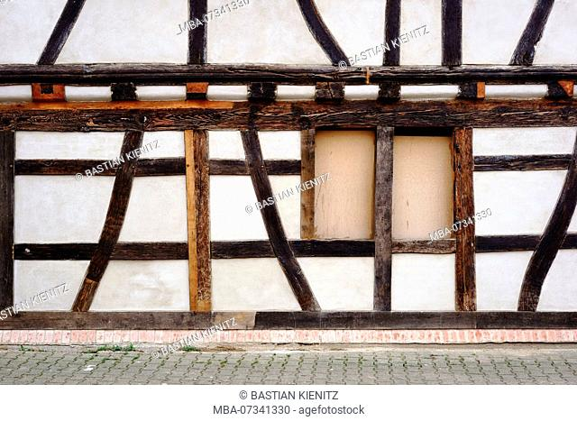 The beam construction and the wooden framework of a half-timbered house with a boarded up window