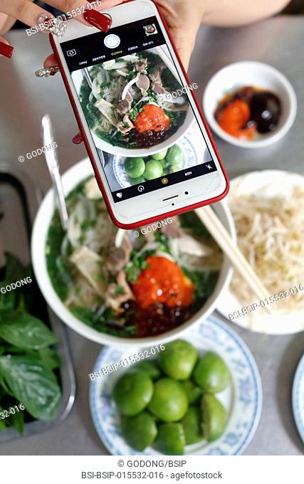 Bowl of Vietnamese noodle soup known as Pho. Woman making picture with smartphone of her meal. Ho Chi Minh City. Vietnam