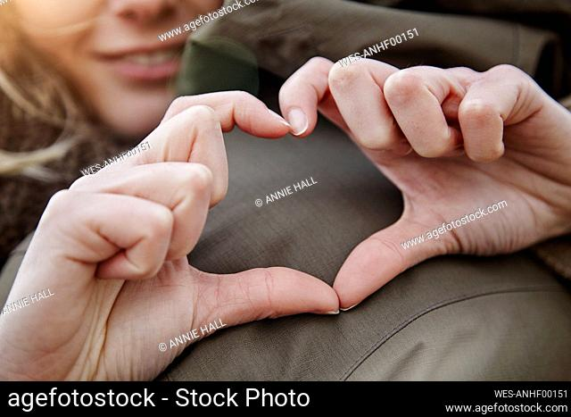 Hands of young woman forming heart, close-up