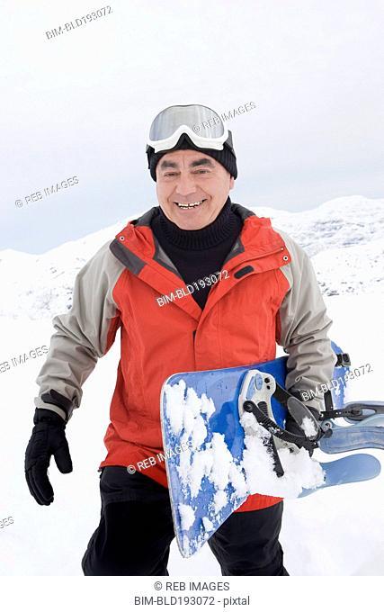 Senior Hispanic man snowboarding