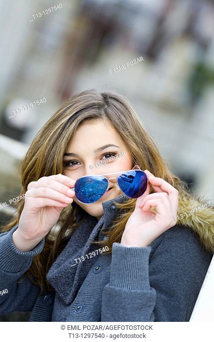 Teenage girl portrait happy with sunglasses in hand