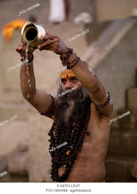 The Ganges River,Varanasi,India,A Sadhu pouring libations into the Ganges