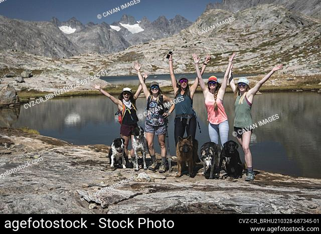 Carefree female friends with dogs standing at Titcomb Basin during vacation