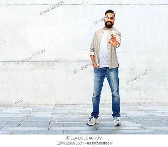 people, gesture and ethnicity concept - happy smiling indian man showing ok hand sign over stone wall background