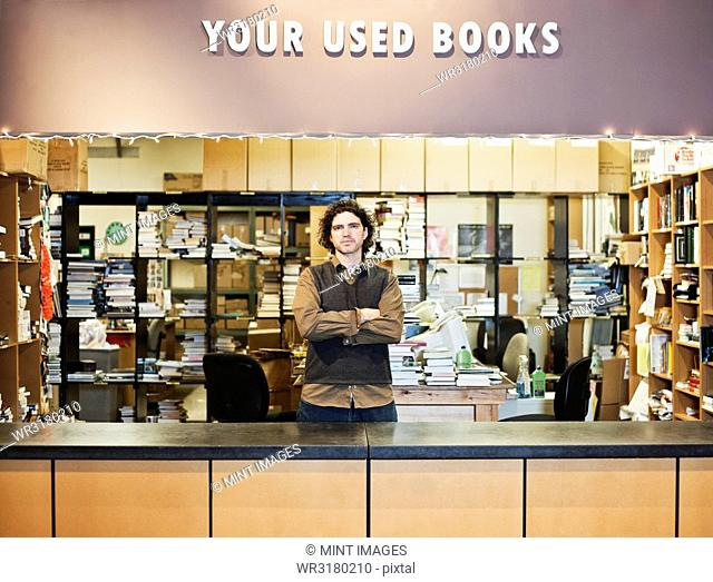 Portrait of a Caucasian male employee of a bookstore working in the Used Books section of the store