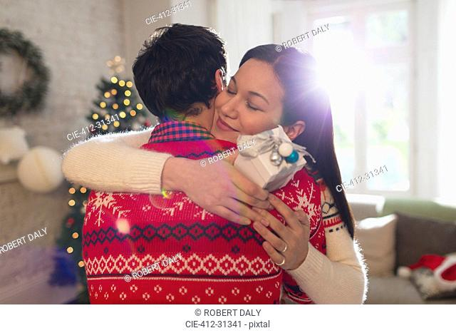 Grateful girlfriend with Christmas gift hugging boyfriend