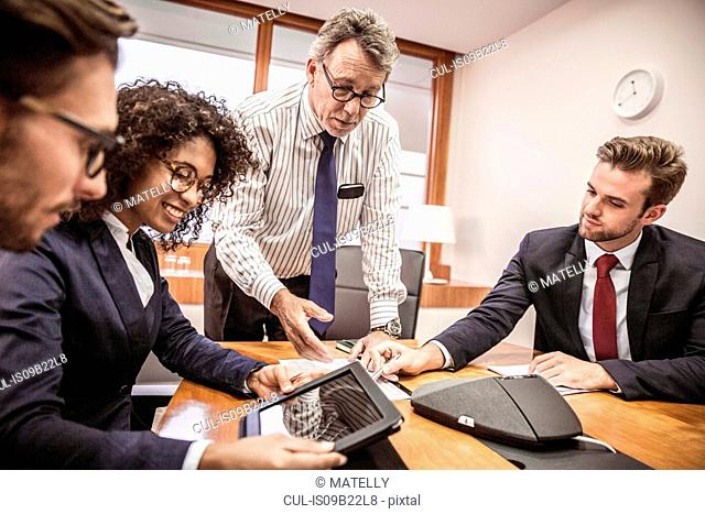 Businessmen and woman using digital tablet at boardroom table meeting