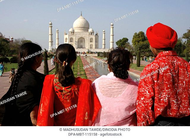 Sikh family viewing at Taj Mahal Seventh Wonders of World on the south bank of Yamuna river , Agra , Uttar Pradesh , India UNESCO World Heritage Site