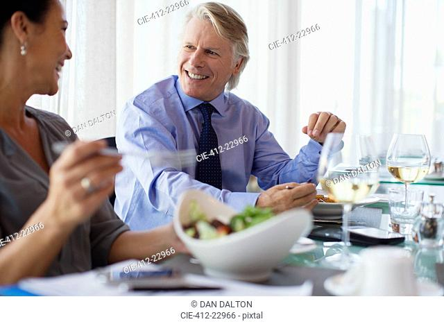 Smiling business people having lunch in restaurant