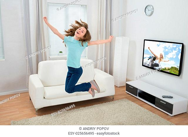 Cute Excited Girl Jumping In Living Room