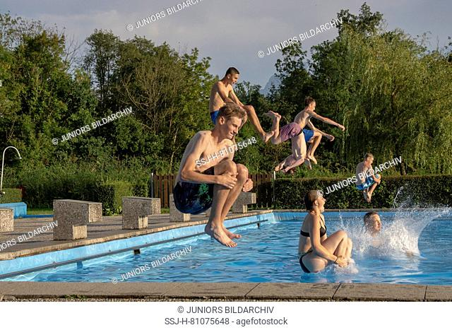 Teens doing a cannonball. Lido in Teisendorf, Bavaria, Germany