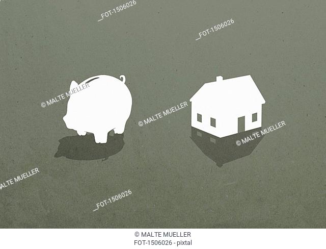 Piggy bank and house against gray background
