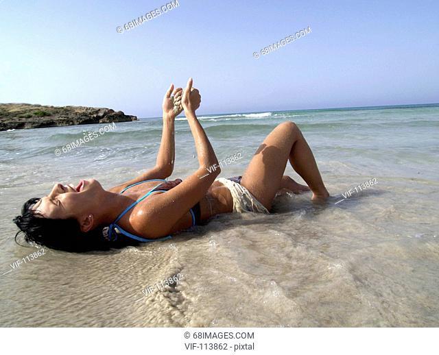 Junge Frau liegt in der Brandung am Strand und l°sst sich vom Wasser umsp?len / Mallorca / *Model-Released*/ Farbraum: ECI-RGB