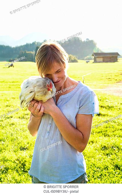 Woman carrying rooster in countryside, Sonthofen, Bayern, Germany