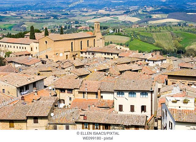 Aerial view of the village of San Gimignano with orange tiled rooftops of the houses, church of St  Augustine, and Tuscan countryside in the background