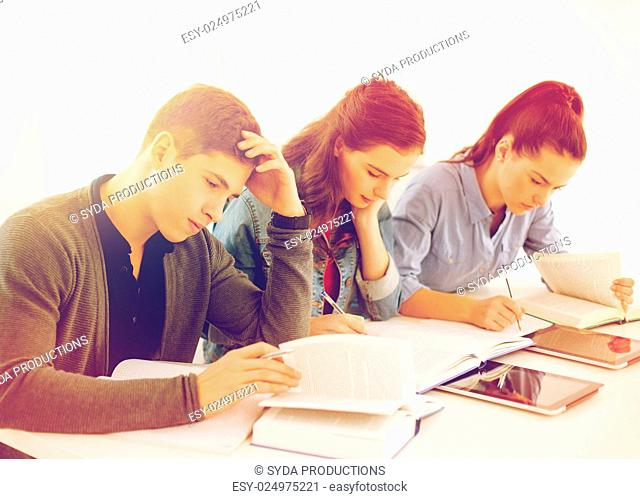 school and education concept - group of tired students with notebooks at school