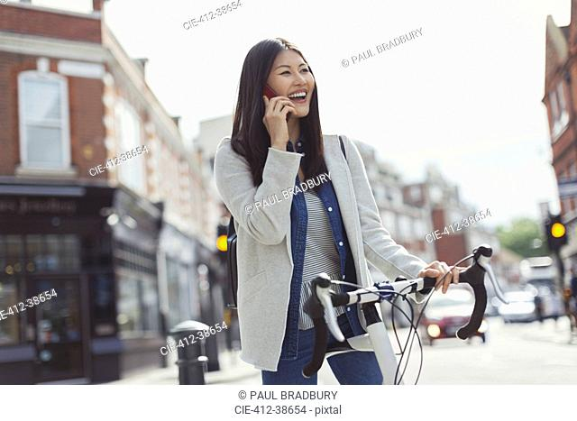 Smiling young woman commuting on bicycle, talking on cell phone on sunny urban street