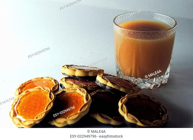 Orange juice and cookies on tablecloth