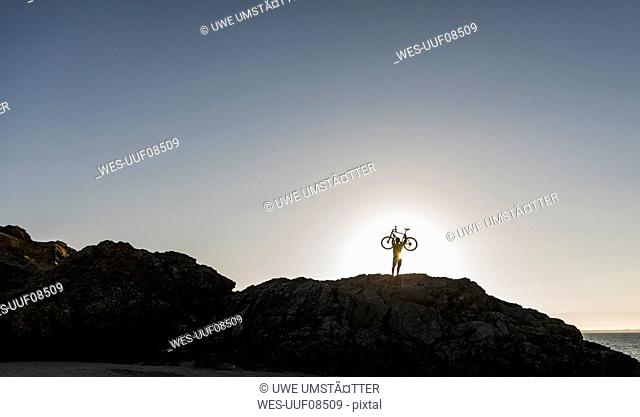 France, crozon peninsula, mountainbiker lifting up his bike at sunset