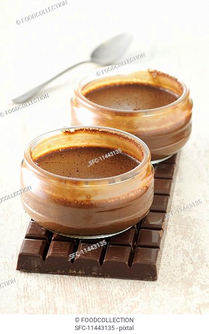 Two bowls of chocolate mousse on a bar of chocolate