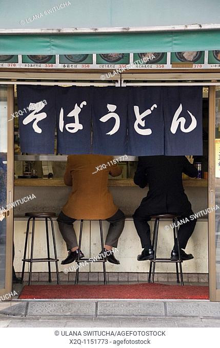 Two men eating soba udon at a restaurant Tokyo Japan