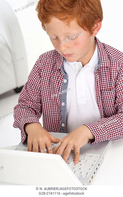 little boy typing on the keyboard of his laptop with concentration