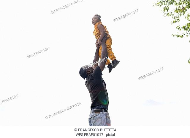 Father lifting up happy daughter