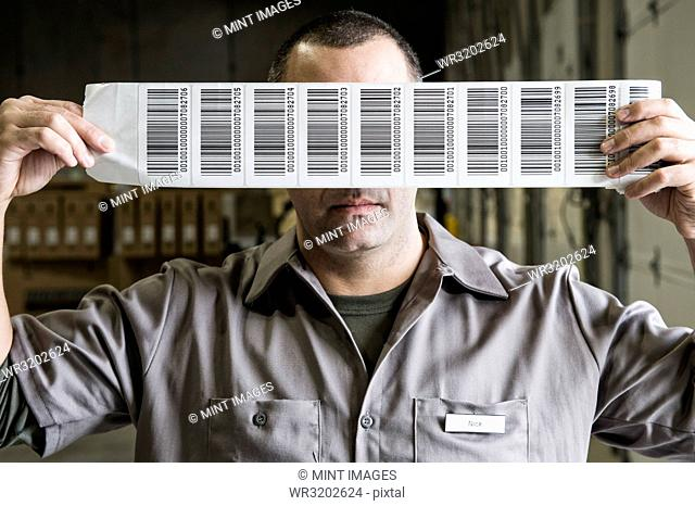 A warehouse worker holding up a sheet of bar code shipping labels in a distribution warehouse