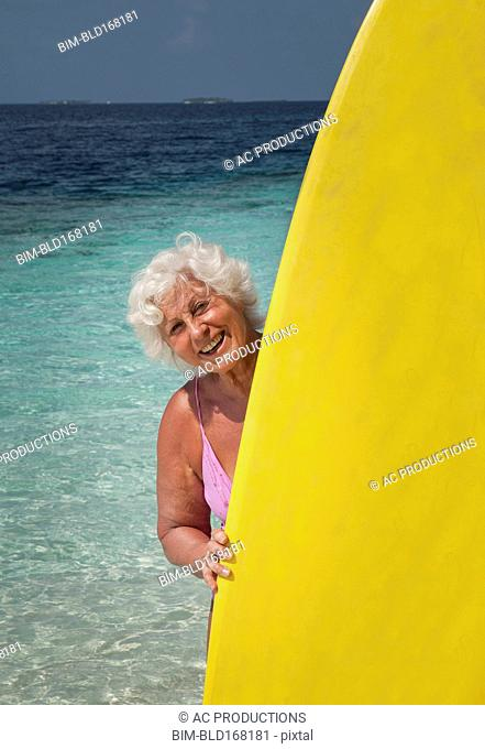 Older Caucasian woman holding surfboard on beach
