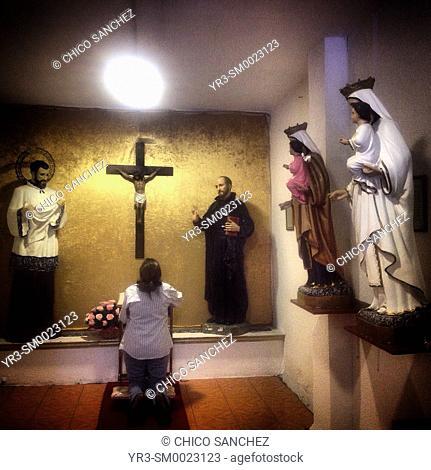 A woman prays to Jesus Christ in a small chapel in the Iglesia de Fatima church in Colonia Roma, Mexico City, Mexico