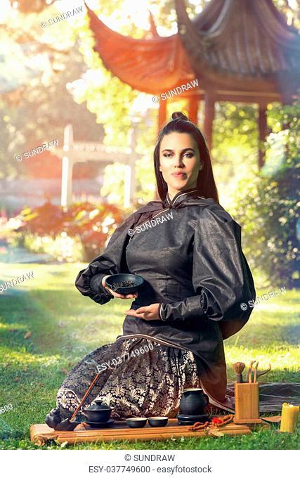 Female tea master making Chinese tea ceremony in garden