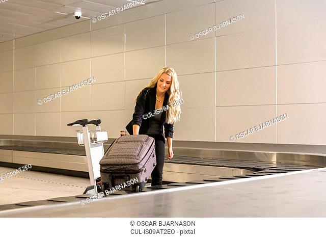 Mid adult woman collecting luggage from baggage claim area in airport and loading trolley