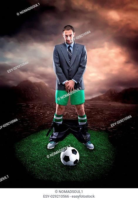 Businessman in sportwear protecting his genitals looks at the football